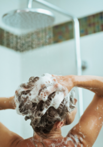 Woman washing her hair with shower head